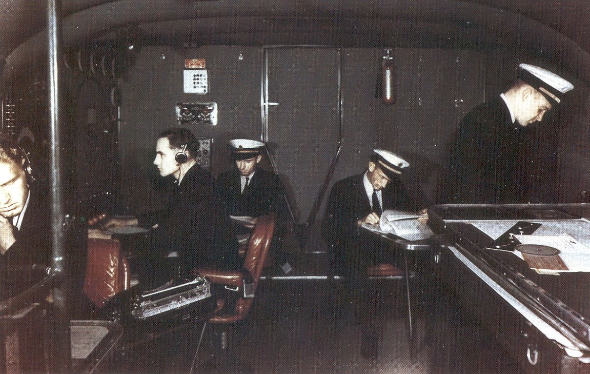 Boeing B314 Rear of cockpit.  Navigator, extreme left, Flight Engineer on left with headphones, reserve officers center rear at planning tables, Navigator or right next to plotting table