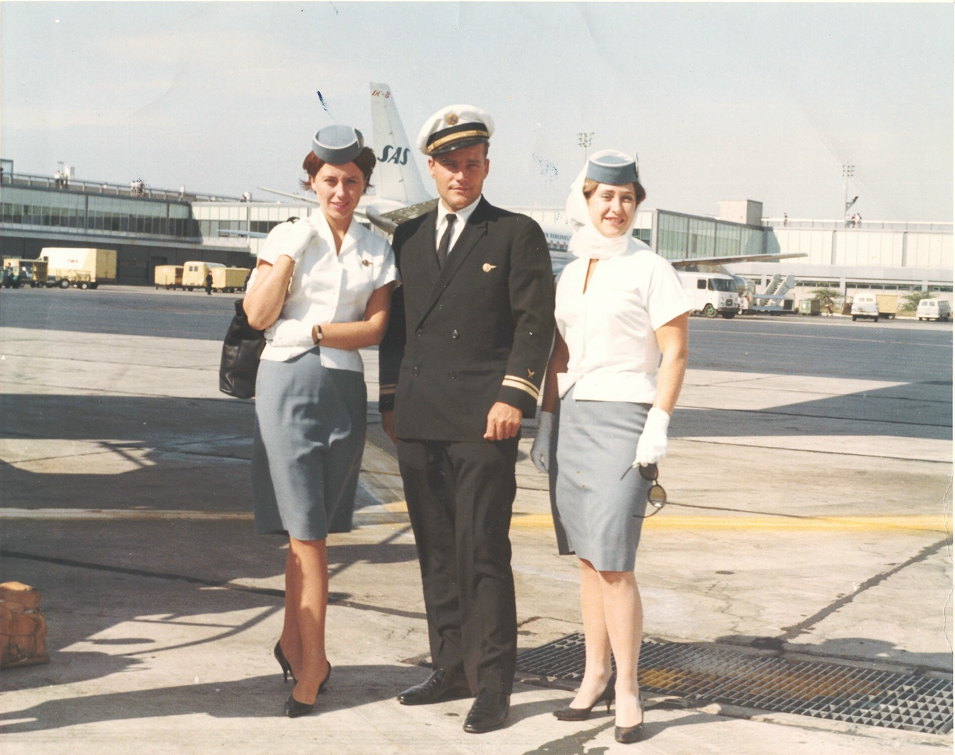 1959 Purser Ray LeDour poses with two stewardesses at New York Idlewild Airport.