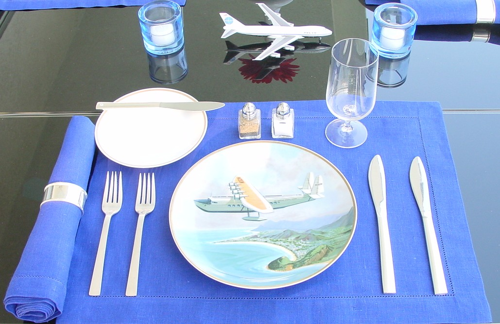 A close up of one of 6 commemorative aircraft plates issued by Pan Am in 1979 in a brunch setting.