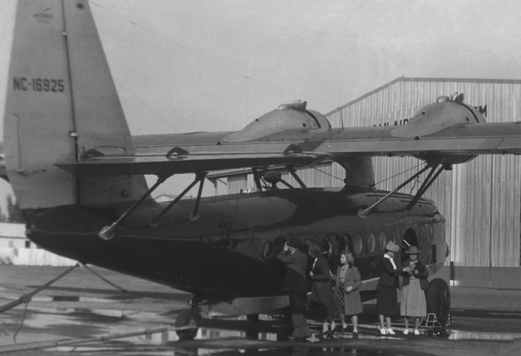 1930s Pan Am Sikorsky S43 flying boat tail number  NC16925 with passengers by the aircraft.