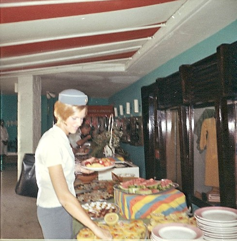 1967 Bernadette Degroote enjoys a hotel buffet lunch during a multi-hour transit on St. Croix