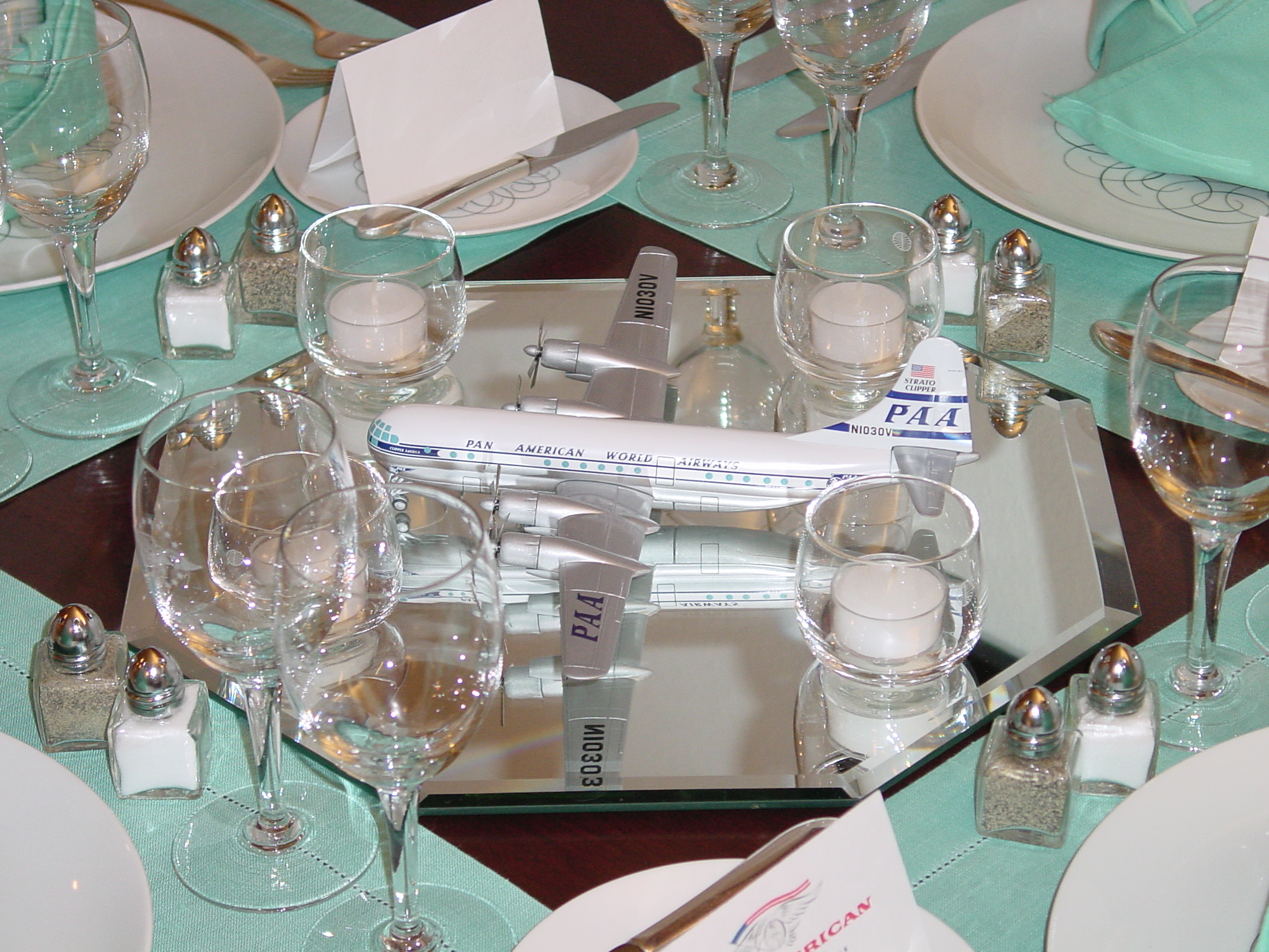 A model of a Boeing B377 'Stratocruiser' make a great center piece for a 1950s President Special table setting with Rosenthal 'Script' pattern plates.