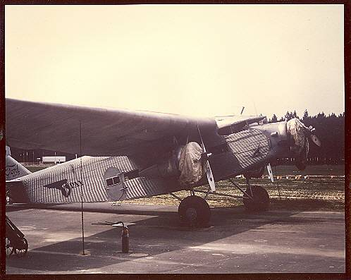 A Pan Am Ford Tri-Motor with engines covered parked on an airport ramp.  Notice the two fire extinguishers under the wing.  Due to stagnant fuel in their components early aircraft engines were prone to start up fires.