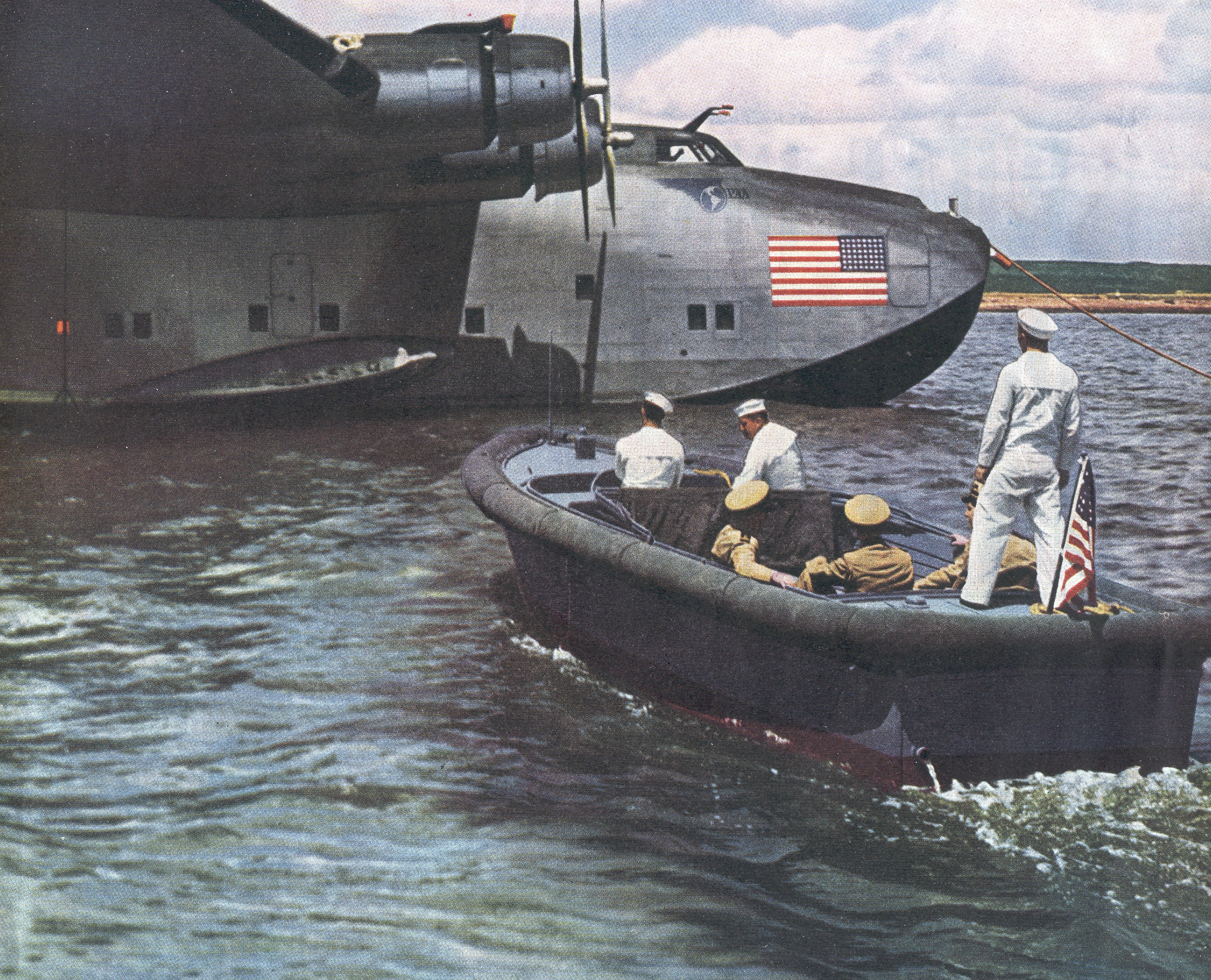 1940s  Navy Launch approaching a moored Boeing B314.  During World War II Pan Am's entire B314 fleet was operated on behalf of the United States Navy moving critical personell and supplies around the world.