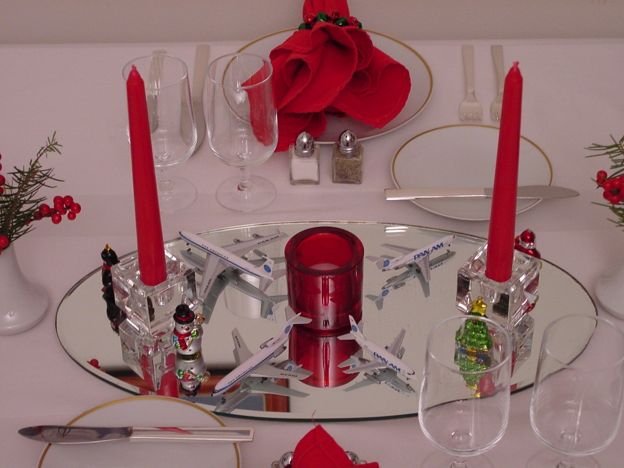 Mini models and red candles are the center piece for this dinner setting with 1970s 'Gold Rim' china.
